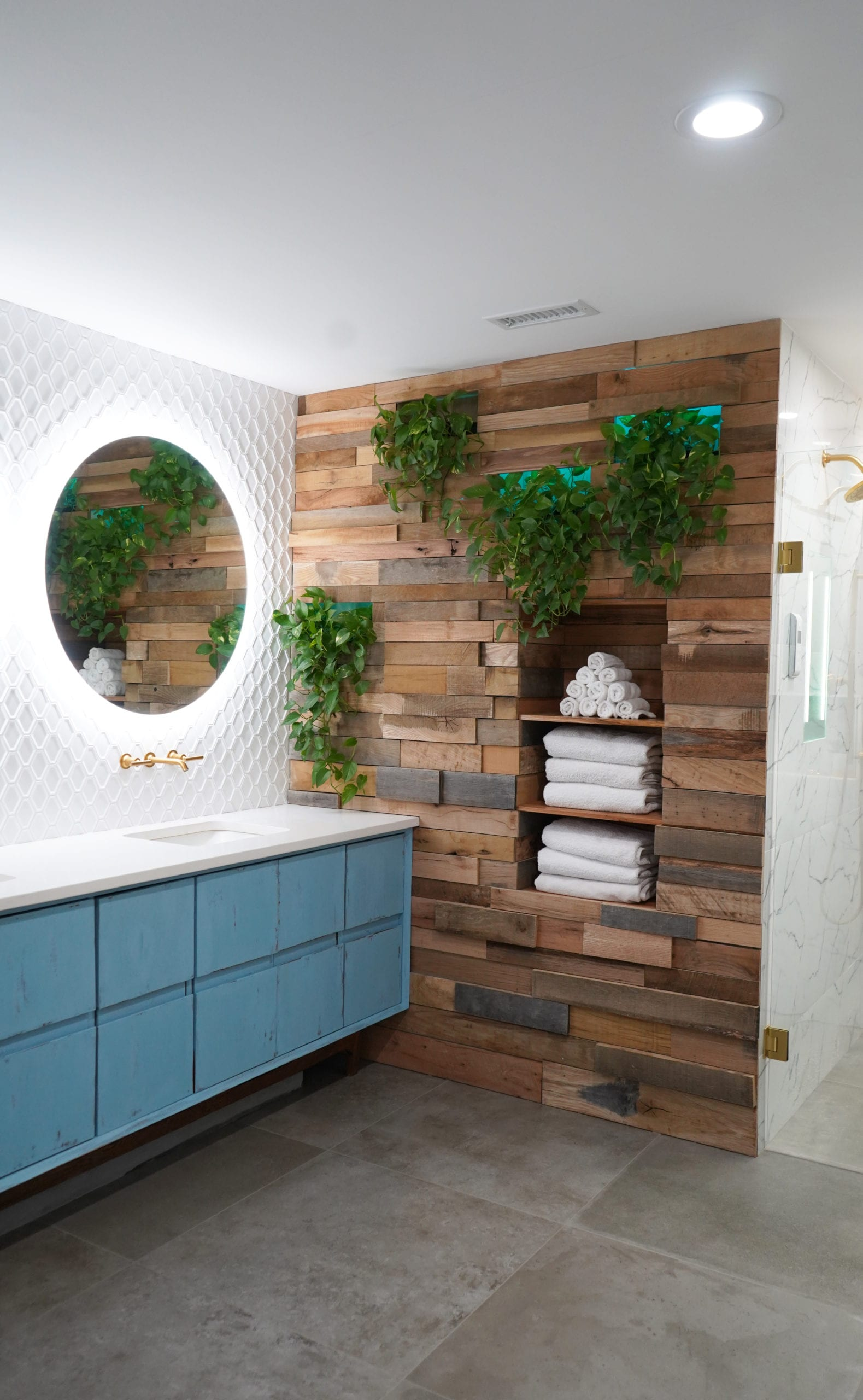 Bathroom Design and Remodel in Atlanta with contemporary vanity, marble tile, walk in shower, gold shower, gold faucets, wood wall, white tile, round mirrors.