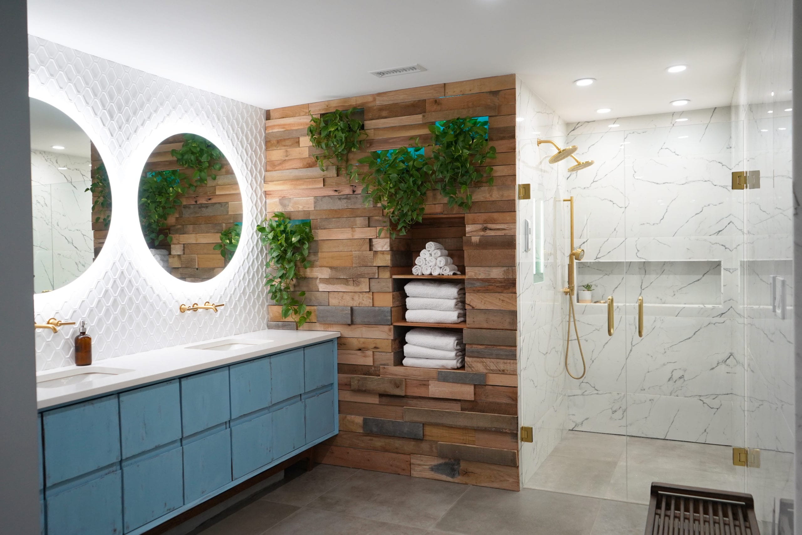 Bathroom Remodel in Atlanta with contemporary vanity, marble tile, walk in shower, gold shower, gold faucets, wood wall, white tile, round mirrors.